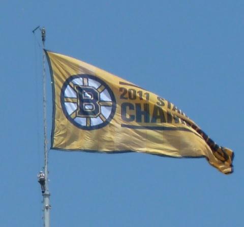 Bruins flag on Hancock Building with man underneath