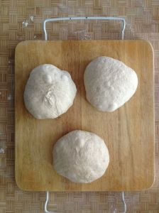 after turning the risen dough out onto a lightly floured surface, cut into three segments and roll into a tight ball